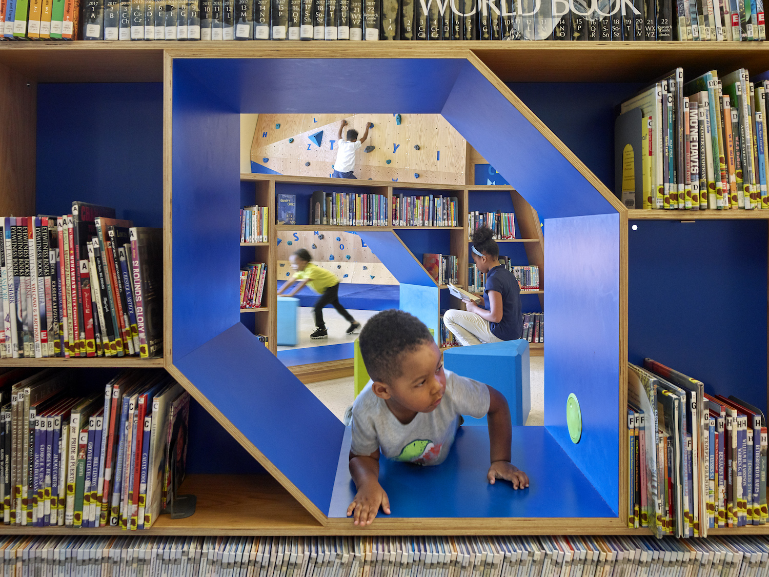 Child crawls through a play area built into bookshelves at branch of the Free Library of Philadelphia