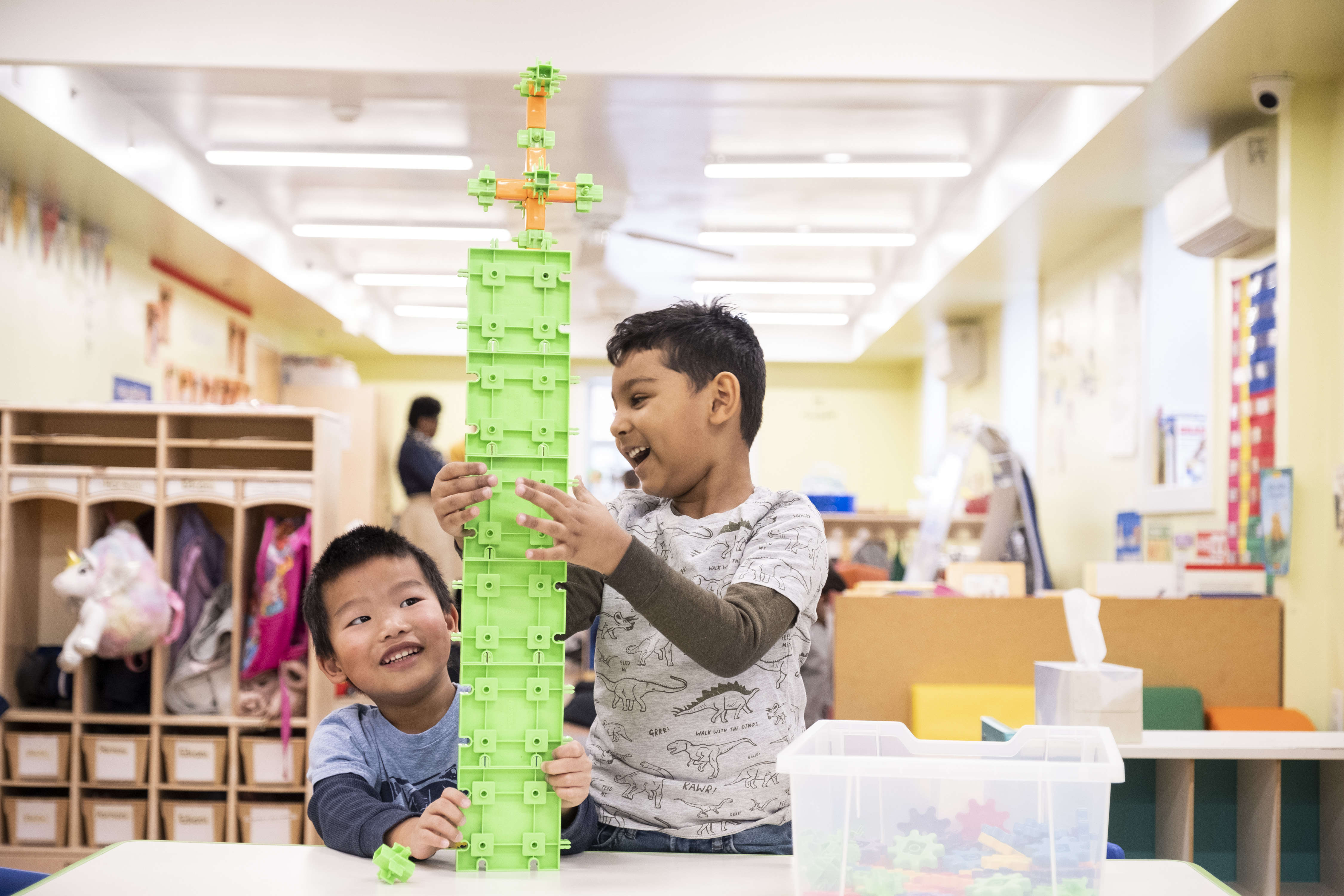 Two children have fun in the classroom with building blocks