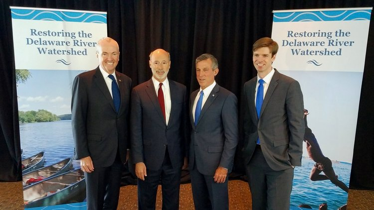 Governor Wolf and associates standing in front of Restoring the Delaware Watershed banners