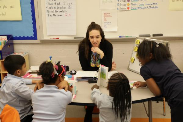 Teacher sits across the table from four of her students who are holding picture books