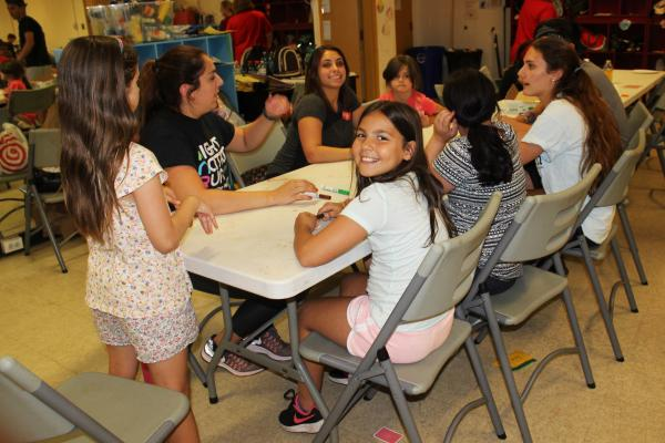 A group of young girls sit at a table at an after school program